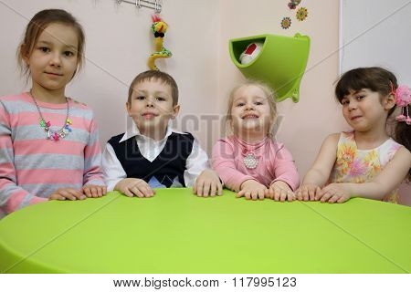 Four cute children are put their hands on the green table.