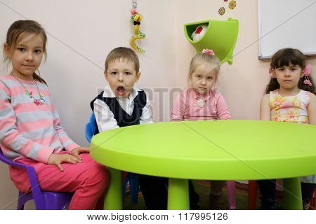 Four cute children are sitting at the green table.