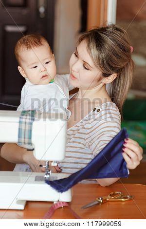 Mother with a baby shows her work, sewing at home. Raising children, child care, nanny.