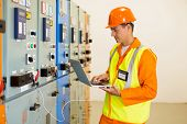 Постер, плакат: experienced electrician working on laptop in substation