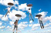 Behind Flying Four Friends With Umbrellas On White, Fluffy Clouds In Blue Sky Collage poster