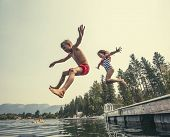 Kids jumping off the dock into a beautiful mountain lake. Having fun on a summer vacation at the lak poster
