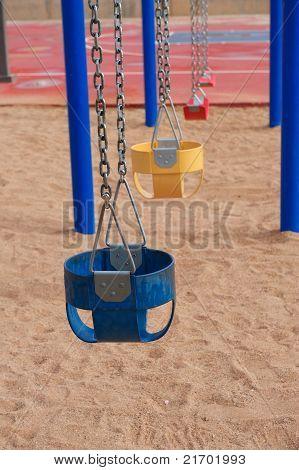 Coloridos columpios vacíos en arena