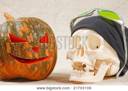 The big cheerful halloween pumpkin and skull with sigarette