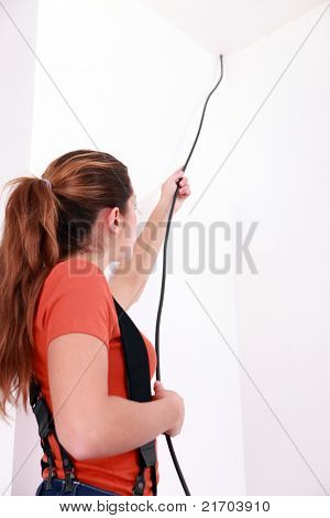 handy-woman pulling a black wire coming from the ceiling
