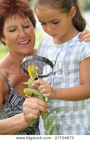 a 55 years old woman and a little looking a yellow flower with a magnifying glass