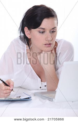 Young woman using a laptop computer and  a pen and paper