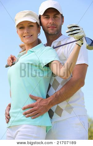 a woman with a golf club and a man putting his hands on her waist