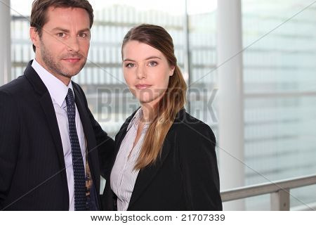 Business couple standing in front of a large window