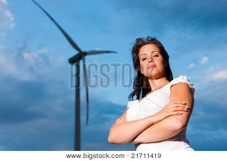 Young woman standing in front of windmill and the blue sky