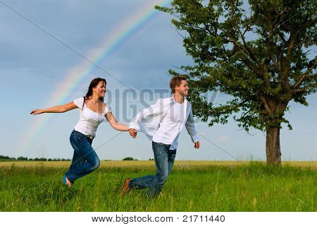 Happy couple running on a meadow in summer; in the background a rainbow