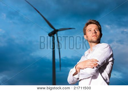 Young man standing in front of windmill and the blue sky