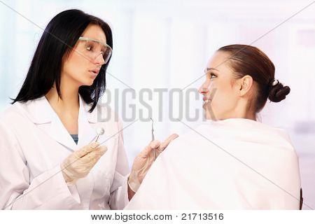 A female dentist is calming a patient in the cabinet