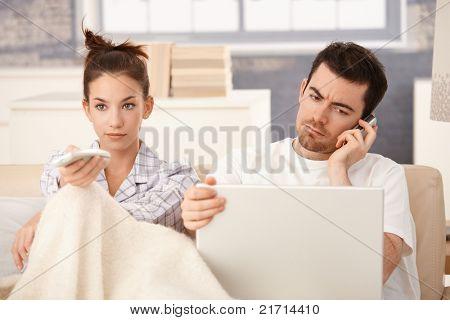 Junges Paar im Bett, Mann mit Laptop und Handy, Frau vor dem Fernseher.?