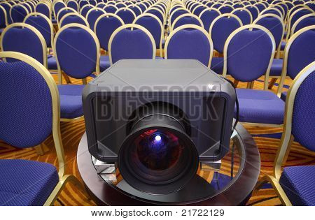 Black projector in center of rows of yellow-blue chairs in bright conference hall