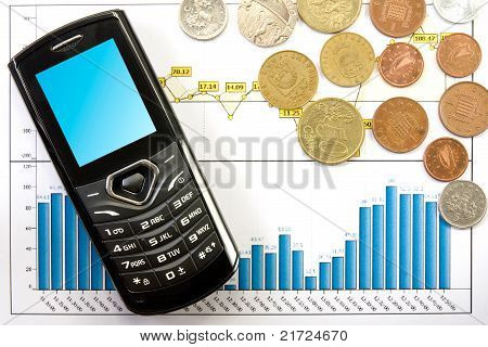 phone  and coins over  business chart