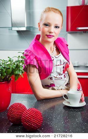 Blond girl in interior of red modern kitchen