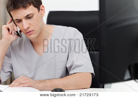 Serious young dentist having conversation on mobile phone