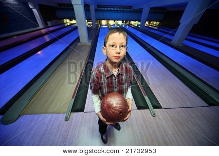 Boy stands with  ball for bowling and looks ahead