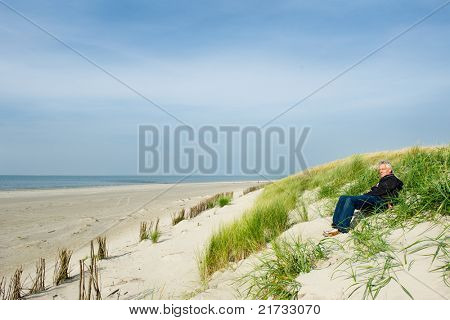 Elderly man is laying in the sand dunes and looking over the beach