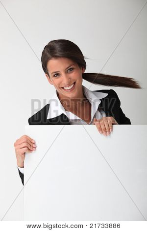 Young smiling woman in a suit with a board blank for your message