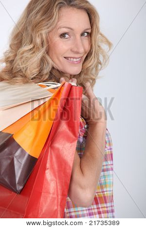 Woman looking over shoulder holding three shopping bags