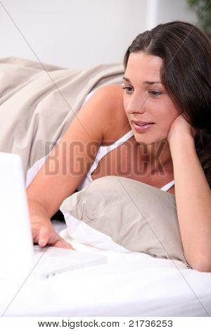 Frau Blick auf ihrem Computer im Bett