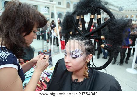 MOSCOW - OCTOBER 2: Visagiste makes makeup for model with punk hairstyle at XVII International Festival