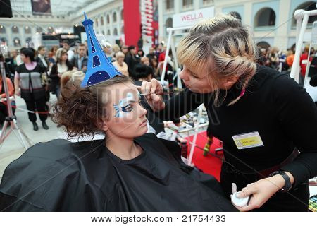 MOSCOW - OCTOBER 2: Visagiste makes body art for model with hat as Eiffel Tower at XVII International Festival