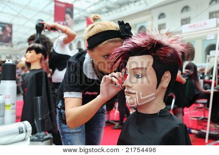 MOSCOW - OCTOBER 2: Hairdresser makes hairstyle for manikin at XVII International Festival