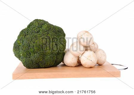 Mushrooms Brocolli On The Cutting Board Isolated On The White Background