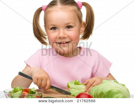 Little Girl Is Cutting Carrot For Salad