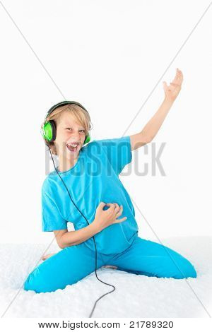 young teen kid playing air guitar and listening to music