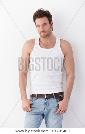 Goodlooking young man wearing undershirt and jeans, standing by wall.?