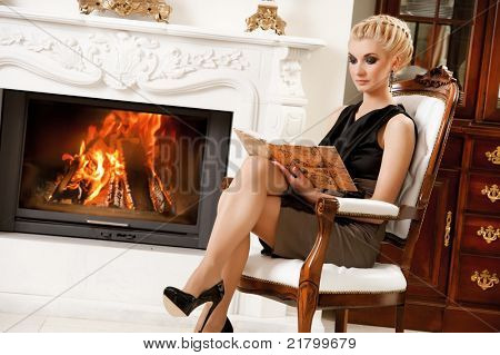Blond lady reading book near fireplace