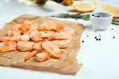Parchment with tasty shrimps on table poster