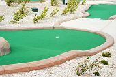 stock photo of miniature golf  - closeup of a miniature golf course with pebbles - JPG