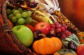 stock photo of cornucopia  - Thanksgiving cornucopia filled with autumn fruits and vegetables - JPG