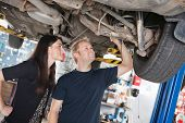 stock photo of auto repair shop  - Young mechanic and woman looking at machine of car in auto repair shop - JPG