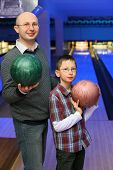 Father and son in glasses stands sideways and holds  balls for bowling