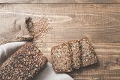 A Loaf Of Fresh Rustic Whole Meal Rye Bread, Sliced On A Wooden Board, Rural Food Background. Top Vi poster