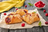 Parchment with delicious puff pastries on wooden table poster