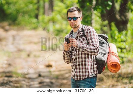 poster of Hipster Young Man With Backpack Using Smart Phone On Beautiful Nature.travel Concept. Outdoor Travel