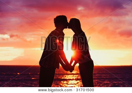 Silhouette of Young Romantic Couple Kissing at Sunset