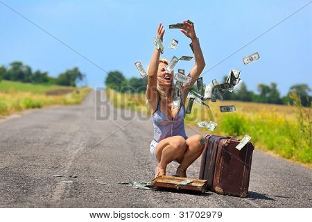 Shocked woman throwing dollars into air on countryside road