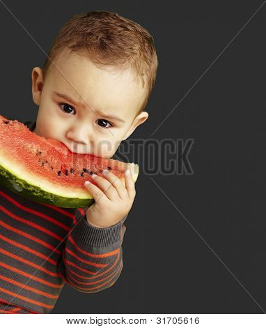portrait of a handsome kid holding a watermelon and sucking over