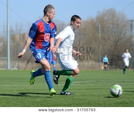 KAPOSVAR, HUNGARY - MARCH 17: Adam Menyhert (in blue) in action at the Hungarian National Championship under 18 game between Kaposvar(white)  and Videoton (blue) March 17, 2012 in Kaposvar, Hungary.