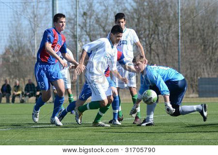 KAPOSVAR, HUNGARY - MARCH 17: Edvard Rusak (R) in action at the Hungarian National Championship under 18 game between Kaposvar(white)  and Videoton (blue) March 17, 2012 in Kaposvar, Hungary.