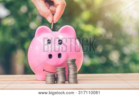 poster of Hand Putting A Coin Into Piggy Bank. Planning Savings Money Of Coins To Buy A Home Concept Concept F