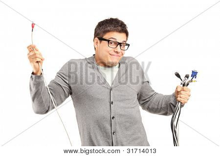 A confused male holding electronic cables isolated on white background